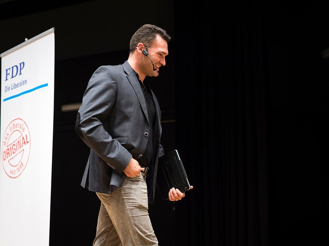 Marcel Dobler, im Hintergrund ist ein FDP-Logo sichtbar
