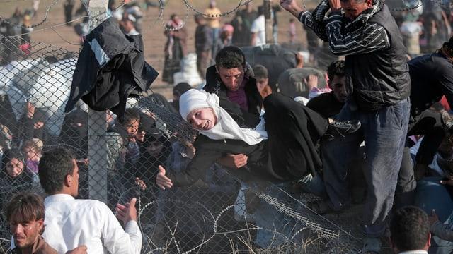 Verzweifelte Menschen klettern über einen Zaun.