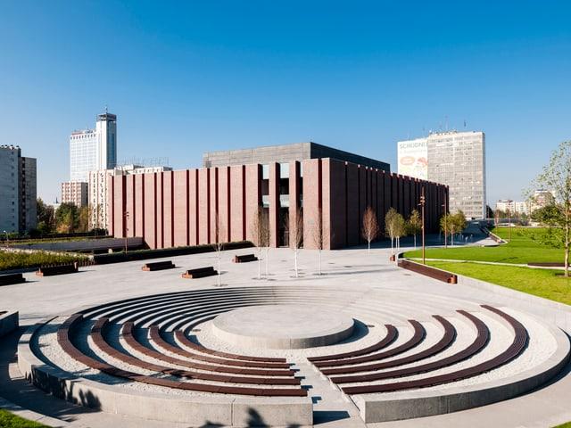 Kubistisches Gebäude aus dunkelrotem Backstein steht in einer modernen Parkanlage.
