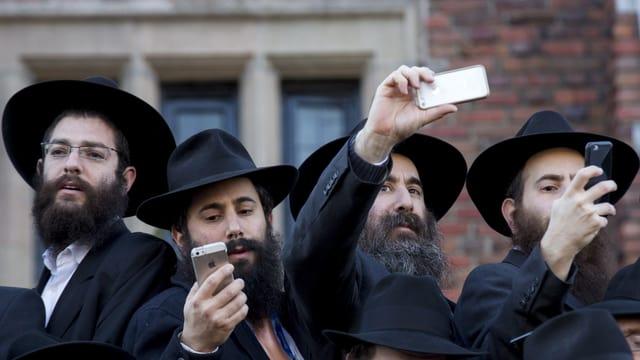Chassidische Juden mit Bärten, schwarzen Hüten und Smartphones
