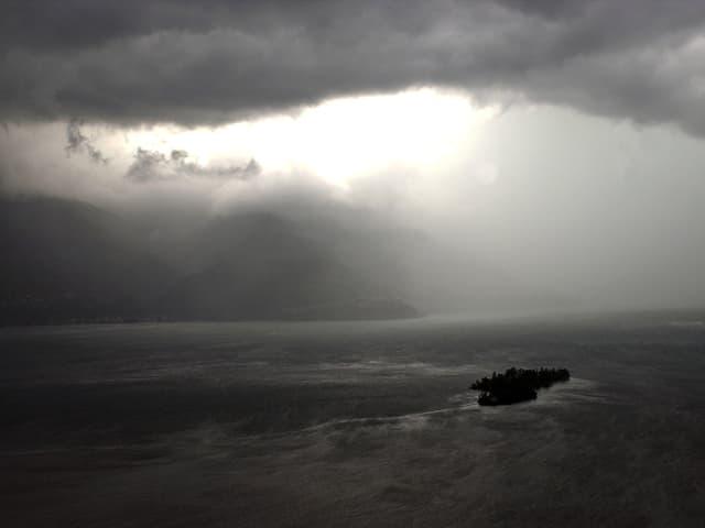 Im Lago Maggiore sind die Brisagoinseln zu sehen. Bedrohlich schwarzer Himmel und dichte Regenschleppen schränken die Sichtweite stark ein.