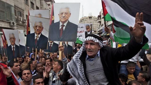 Palästinenser demonstrieren mit Fahnen und Bildern von Abbas.