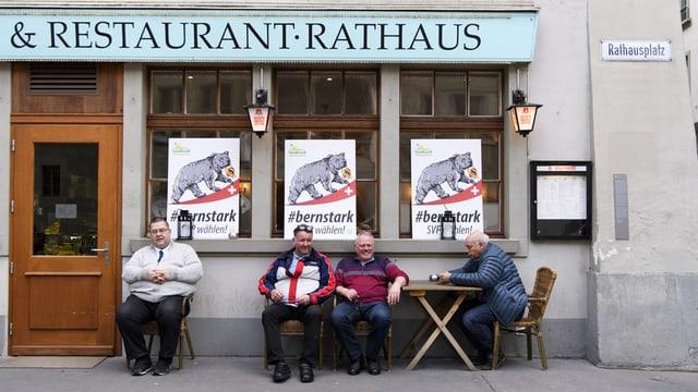 Vier Männer sitzen vor dem Restaurant Rathaus