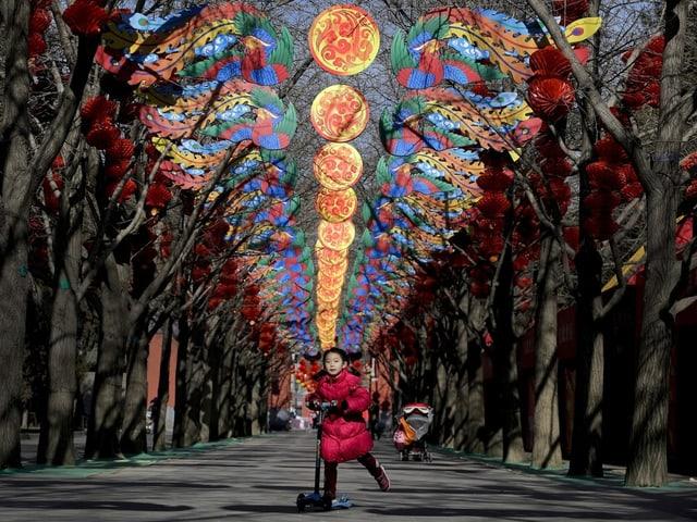 Ein kleines Mädchen fährt mit einem Scooter durch eine mit vielen farbigen Girlanden geschmückte Alee.