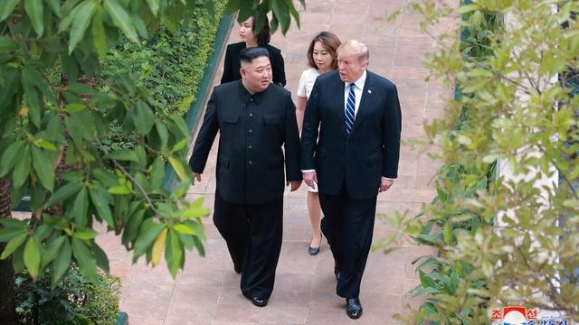 Trump und Kim gehen nebeneinander und sprechen zusammen.