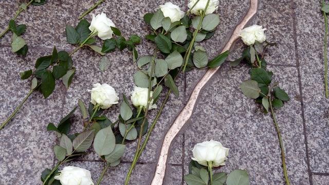 Goldener Riss am Boden und weisse Rosen.