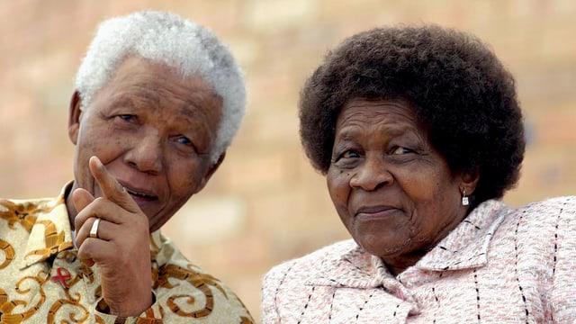 Eine Frau und ein Mann sitzen nebeneinander und schauen in die Kamera. Der Mann ist Nelson Mandela.