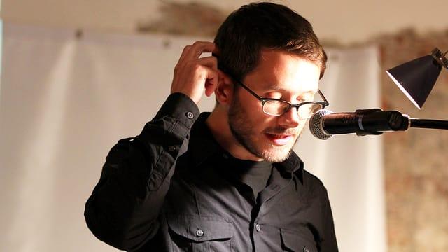 Ein Mann hinter einem Mikrophon liest aus einem Buch