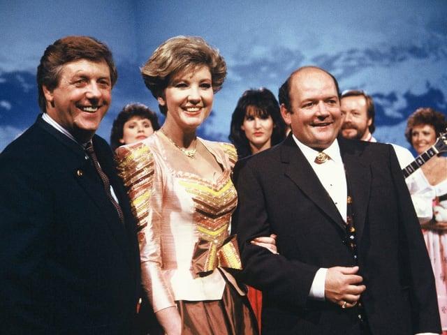 Zwei Männer und eine Frau während einer Fernsehsendung.