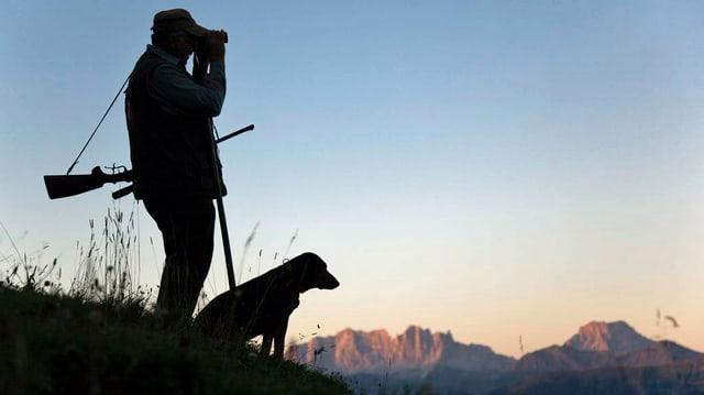 Silhouette eines Jägers mit seinem Hund auf einem Berghang.