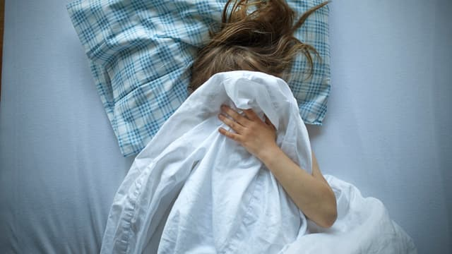 Mädchen mit Decke über Kopf.