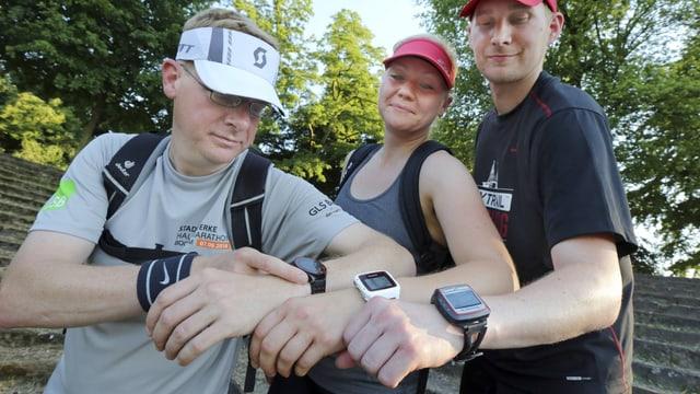 Drei Hobbysportler zeigen ihre Uhren, die den Puls und andere Körperdaten erfassen.