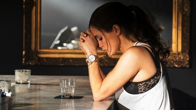 Frau sitzt am Tisch und hat die Hände vor dem Gesicht.