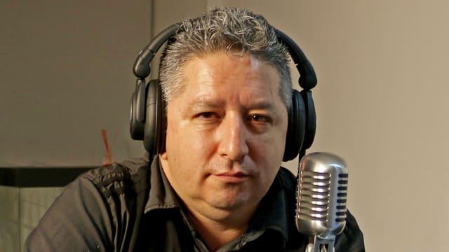 Herbin Hoyos mit Kopfhörer vor einem Mikrofon.