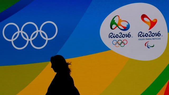 Die Symbole von Olympia und Rio 2016 mit den Schatten einer Frau.