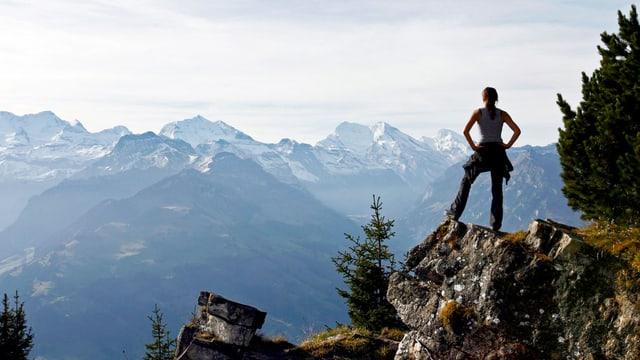 Eine Wanderin steht auf einem Bern und blickt auf die umliegenden Berge.