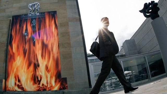 An der Wand des Kunsthauses hängt ein überlebensgrosses Plakat, auf dem Flammen dargestellt sind. Im Vordergrund läuft ein schwarz gekleideter Mann am Museum vorbei, dem die Sonne ins Gesicht scheint.