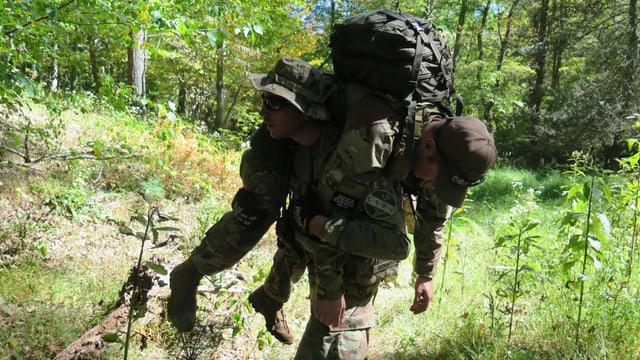 Ein Miliz-Soldat transportiert einen Kameraden auf der Schulter.