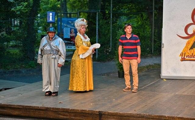 Drei Personen, eine mit einem Infozeichen auf dem Kopf stehen auf einer Bühne