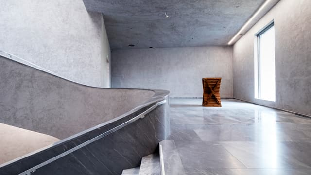 Eine Treppe, die von rechts nach links abbiegt, hinten im Gang ein Holzobjekt.