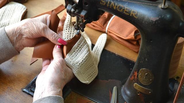 Eine Frau näht einen Handschuh an einer alten Singer-Nähmaschine.