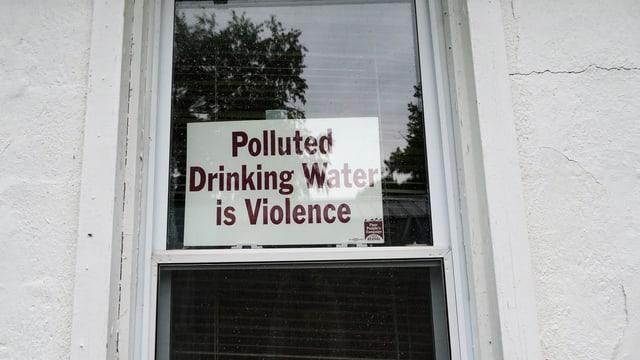 Protestschild gegen das verschmutzte Trinkwasser an einer Tür.