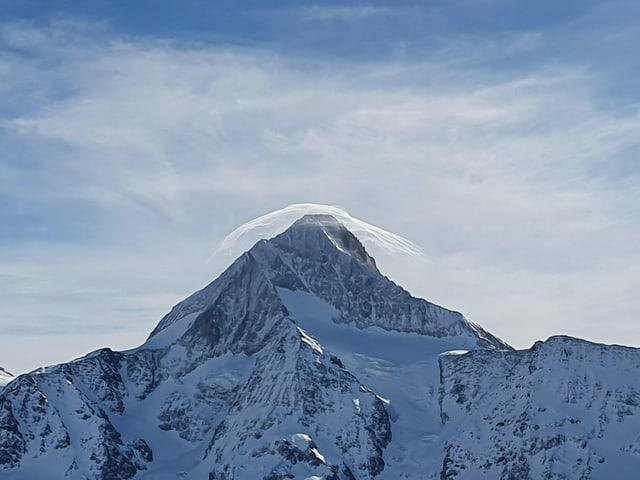 Eine Wolke wie ein Hut über einem Berg.
