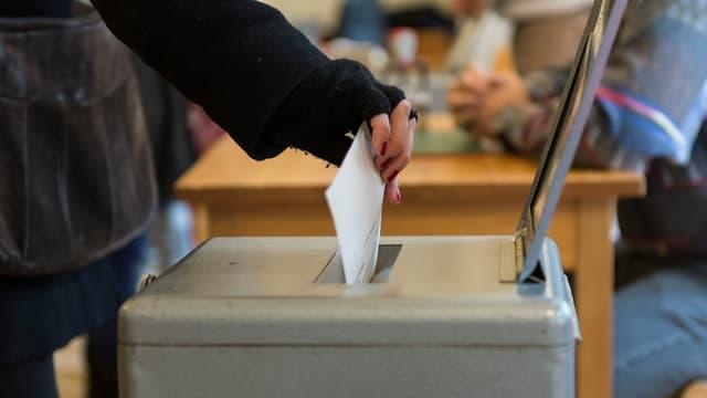Eine Frau wirft einen Wahlzettel in eine Urne.