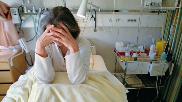 Eine Frau sitzt auf einem Krankenbett und bedeckt ihr Gesicht.