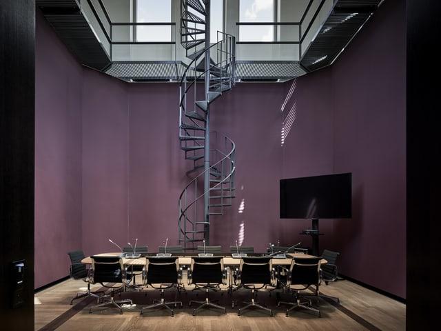 Ein lila gestrichenes Sitzungszimmer mit hoher Wendelteeppe.