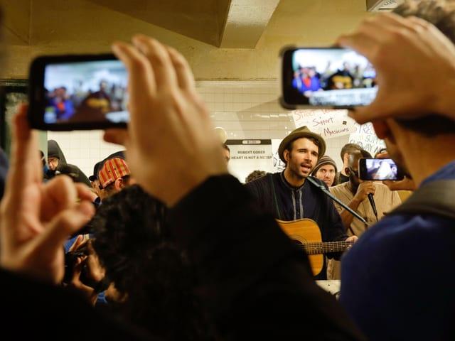 Menschen filmen die Demnstration und den Musiker mit den Handys.