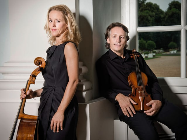 Ein Frau mit Cello stehend, ein Mann mit Violine sitzend.