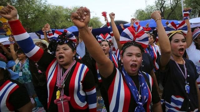 Demonstrantinnen in den thailändischen Farben recken Fäuste in die Höhe