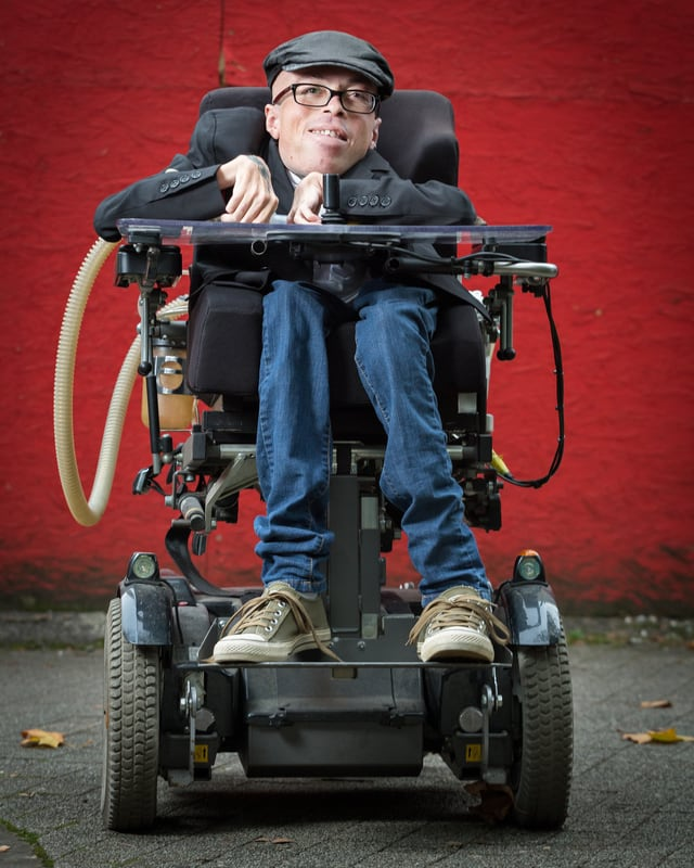 Mann im Rollstuhl vor roter Wand