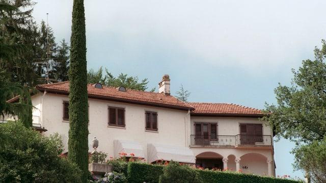 Ein beiges Haus mit einem gut gepflegten Garten um das Haus herum.