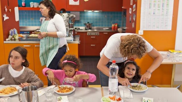Kinder beim Mittagessen mit einem Teller Spaghetti.