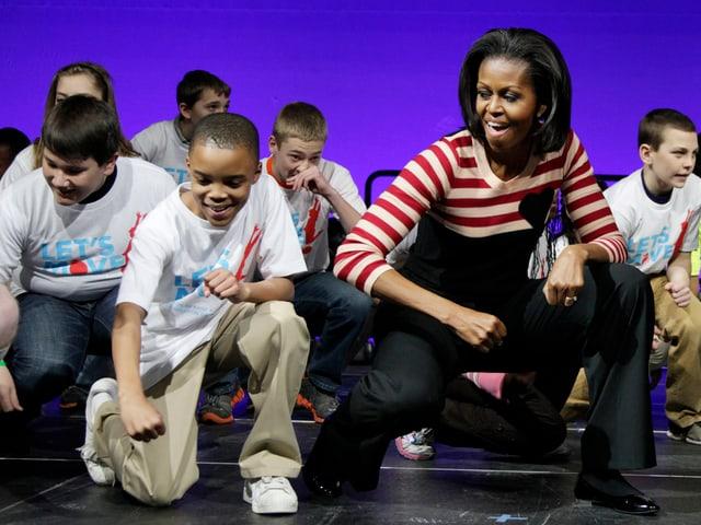 Michelle Obama tanzt mir einer Gruppe Jugendlicher einen Hip-Hop-Move.