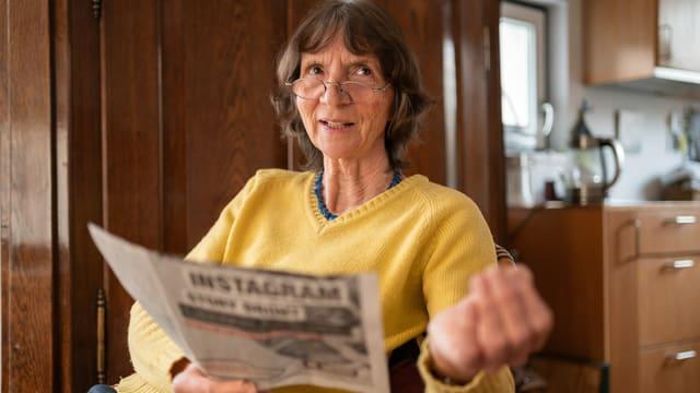 Aleida Assmann mit einer Zeitung in der Hand.