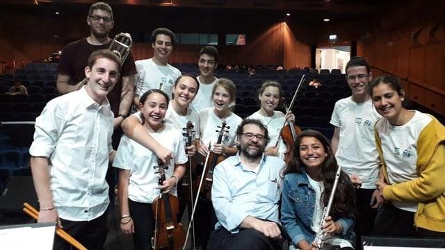 Francesco Lotoro inmitten junger Musiker in einem Konzertsaal