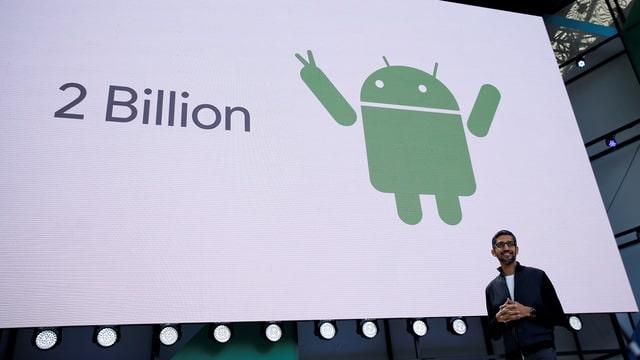Google-CEO Sundar Pichai vor einer Leinwand, darauf das Android Symbol und der Text «2 Billion».