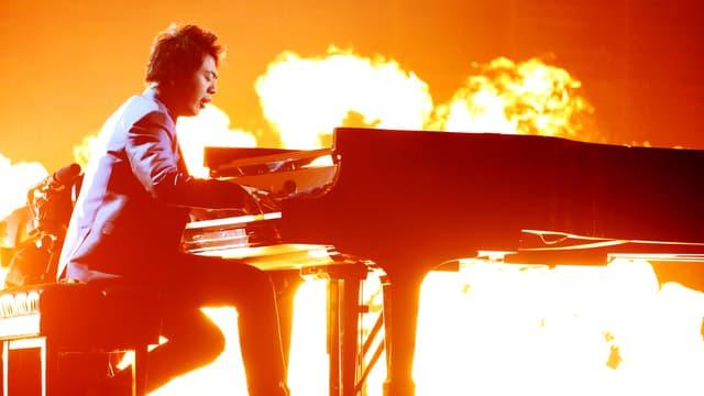 Ein Pianist an einem Flügel vor einem Flammenmeer.