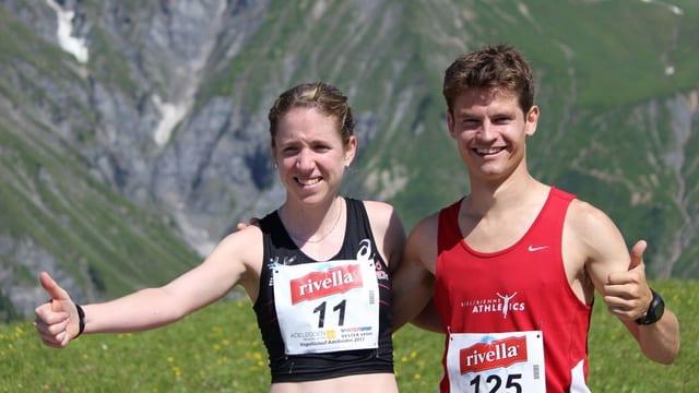 Die Sieger des Vogellisi-Berglaufs, Martina Strähl und Christian Mathy posieren vor der Bergkulisse. Beide halten einen Daumen hoch und strahlen in die Kamera.