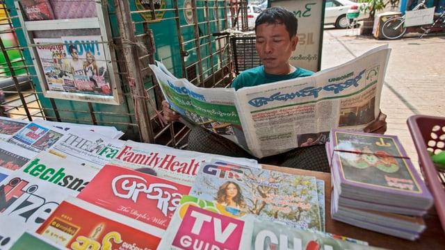 Mann mit burmesischer Zeitung in der Hand an einem Kiosk.