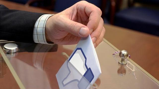 Eine Hand legt eine Abstimmungskarte in eine gläserne Wahlurne. Auf der Karte ist ein nach unten gerichteter Daumen in Facebook-Grafik zu sehen.