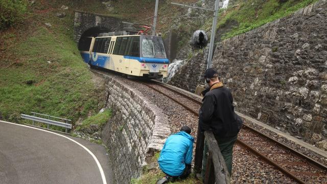 Kameramann und Assistent drehen am Rande der Bahngeleise den herannnahenden Zug.