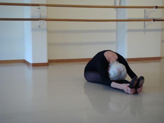 Elsbeth Oberer-Gmür sitzt am Boden und beugt sich weit nach vorn