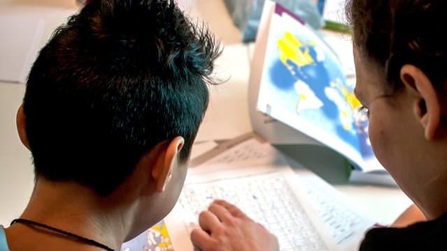 Ein Frau schaut mit einem Jungen ein Schulbuch an.