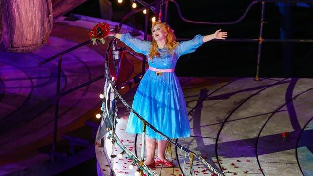 Eine Frau steht im blauen Kleid, mit Rosen und ausgebreiteten Armen auf einer Bühne.