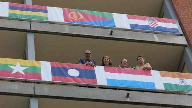 Vier Personen stehen auf einem Wohnblockbalkon und schauen uns an.