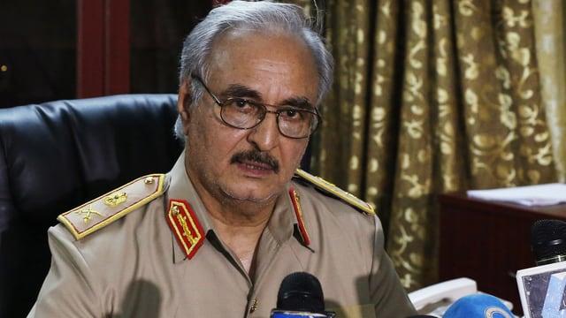Haftar sitzt in seiner Generalsuniform vor mehreren Mikrofonen und blickt in die Kamera.